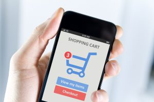Mens hand holding modern mobile phone with online shopping application on a screen.